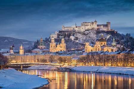 rivers mountains: Beautiful view of the historic city of Salzburg with Salzach river in winter during blue hour, Salzburger Land, Austria Stock Photo