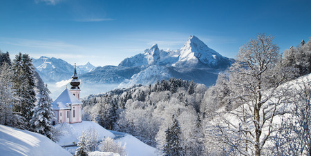 Panoramic view of beautiful winter landscape in the Bavarian Alps with pilgrimage church of Maria Gern and famous Watzmann massif in the background, Nationalpark Berchtesgadener Land, Bavaria, Germany photo