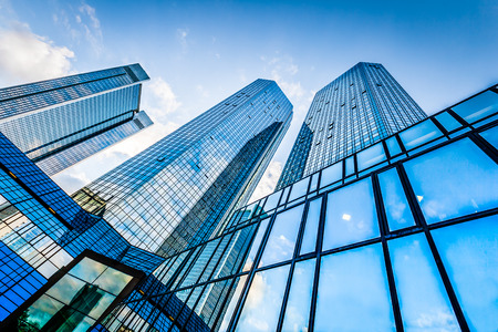 case moderne: Vista dal basso di moderni grattacieli nel quartiere degli affari contro il cielo blu