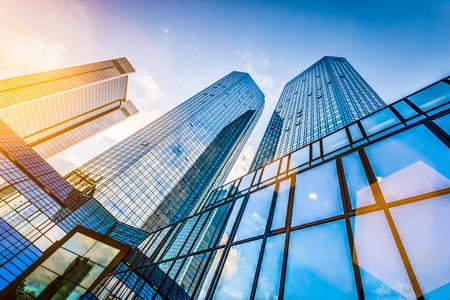 construcci�n: Vista inferior de modernos rascacielos en el distrito de negocios en la puesta de sol con efecto de filtro destello de lente Foto de archivo