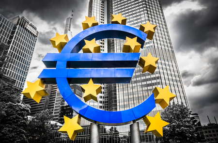 Euro sign at European Central Bank headquarters in Frankfurt, Germany with dark dramatic clouds symbolizing a financial crisis photo