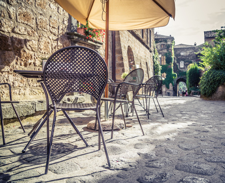 street cafe: Cafe with tables and chairs in an old street in Europe with retro vintage Instagram style filter effect Stock Photo