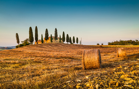 val dorcia: Beautiful Tuscany landscape with traditional farm house and hay bales in golden evening light, Val d Orcia, Tuscany, Italy