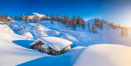 Panoramisch uitzicht op prachtige winter landschap met sneeuw bedekte berg hut in de Alpen in gouden avond licht bij zonsondergang
