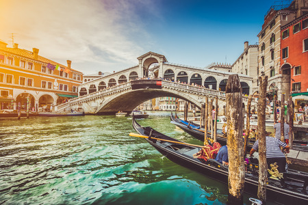 rialto bridge: Panoramic view of famous Canal Grande with famous Rialto Bridge at sunset in Venice, Italy with retro vintage