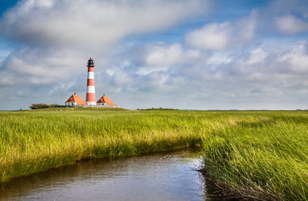 salt marsh: Traditional lighthouse at North Sea with blue sky and clouds