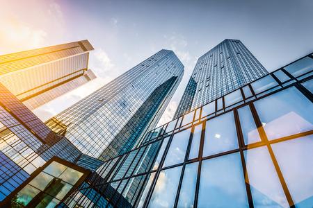 Ansicht von unten auf moderne Wolkenkratzer im Geschäftsgebiet bei Sonnenuntergang mit Lens Flare Filterwirkung