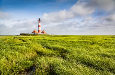 Faro tradizionale a Mare del Nord con cielo azzurro e nuvole Archivio Fotografico - 38391767