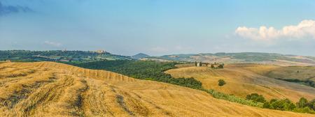 cappella: Colinas y campos de cosecha en la luz dorada de la tarde con la famosa Cappella della Madonna di Vitaleta y el casco antiguo de Pienza, en el fondo, Val d'Orcia, Toscana, Italia