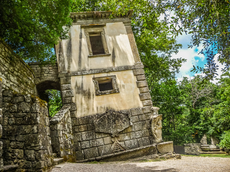 Crooked building at famous Parco dei Mostri Park of the Monsters, also named Sacro Bosco Sacred Grove or Gardens of Bomarzo in Bomarzo, province of Viterbo, northern Lazio, Italy Banco de Imagens