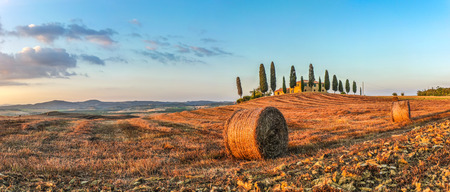 Panoramic view of beautiful Tuscany landscape with traditional farm house and hay bales in golden evening light, Val dOrcia, Italy
