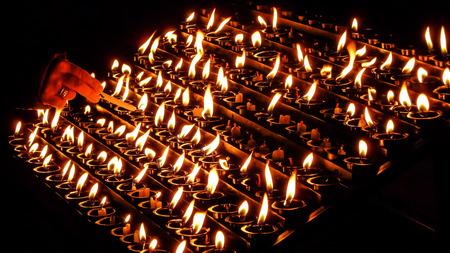 church: Iluminación de ofrecimiento de la mujer de la vela de oración, de sacrificio o velas conmemorativas encendidas en una iglesia