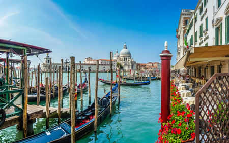 venice canal: Beautiful view of traditional Gondola on Canal Grande with historic Basilica di Santa Maria della Salute in the background on a sunny day in Venice, Italy