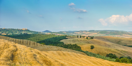 val d'orcia: Rolling hills and harvest fields in golden evening light with famous Cappella della Madonna di Vitaleta and the old town of Pienza in the background, Val dOrcia, Tuscany, Italy Stock Photo