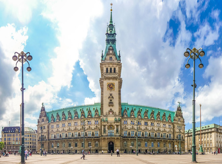 altstadt: Beautiful view of famous Hamburg town hall with dramatic clouds and blue sky at market square near lake Binnenalster in Altstadt quarter, Hamburg, Germany