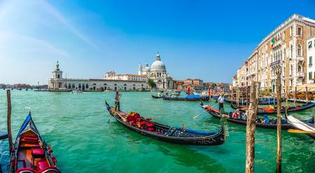 Mooi uitzicht van de traditionele Gondel op Canal Grande met historische Basilica di Santa Maria della Salute op de achtergrond op een zonnige dag in Venetië, Italië
