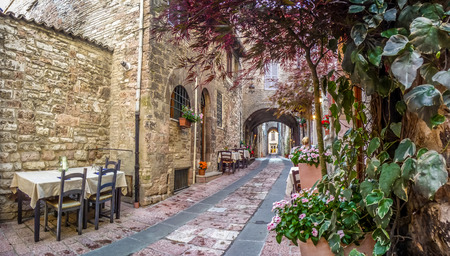 Romantic dinner place in a beautiful alley in the ancient town of Assisi, Umbria, Italy 스톡 콘텐츠