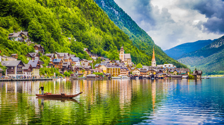 austrian village: Scenic picture-postcard view of famous Hallstatt mountain village with Lake Hallstatt and traditional Pltte boat in the Austrian Alps, region of Salzkammergut, Austria