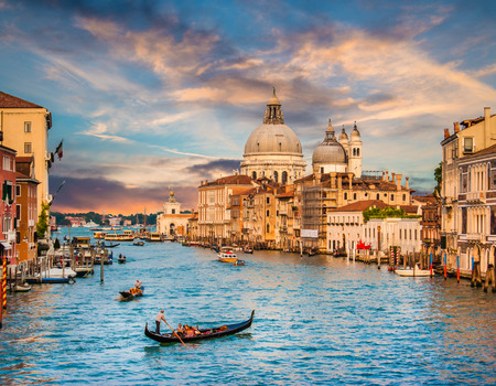 venice: Beautiful view of traditional Gondola on famous Grand Canal with Basilica di Santa Maria della Salute in golden evening light at sunset in Venice, Italy