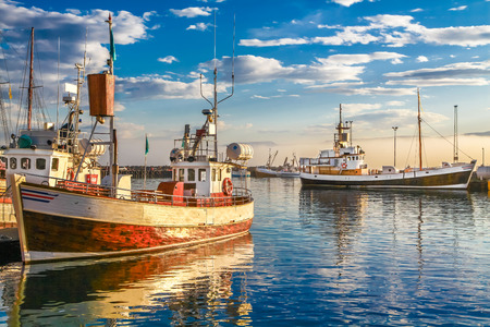 pier: Panoramic view of traditional old wooden fisherman boats lying in harbor in beautiful golden evening light at sunset, town of Husavik, Skjalfandi Bay, Iceland, northern Europe