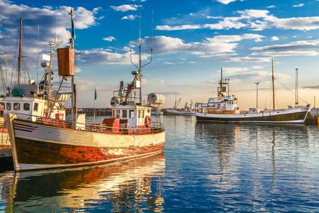 p�cheur: Vue panoramique de vieux bateaux de p�cheurs traditionnels en bois se trouvant dans le port dans la belle lumi�re dor�e du soir au coucher du soleil, ville de Husavik, Skjalfandi Bay, l'Islande, l'Europe du Nord Banque d'images