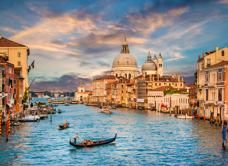iceland: Beautiful view of traditional Gondola on famous Grand Canal with Basilica di Santa Maria della Salute in golden evening light at sunset in Venice, Italy