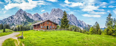 Landschap: Panoramisch uitzicht op prachtige berglandschap in de Alpen met een traditionele houten chalet en verse groene weiden in de lente Stockfoto