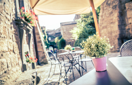 outdoor cafe: Cafe with tables and chairs in an old street in Europe with retro vintage   Stock Photo