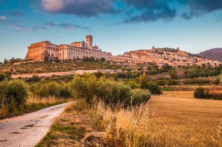 Schöne Aussicht auf die Altstadt von Assisi mit dramatische Wolken im goldenen Abendlicht, Umbrien, Italien