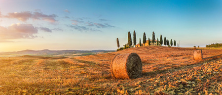 val dorcia: Panoramic view of beautiful Tuscany landscape with traditional farm house and hay bales in golden evening light, Val dOrcia, Italy