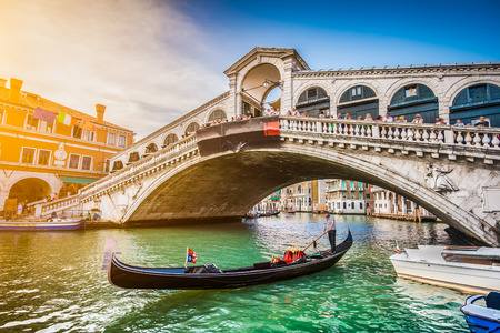 Beautiful view of traditional Gondola on famous Canal Grande with Rialto Bridge at sunset in Venice, Italy