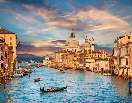 Beautiful view of traditional Gondola on famous Canal Grande with Basilica di Santa Maria della Salute in golden evening light at sunset in Venice, Italy Stock Photo