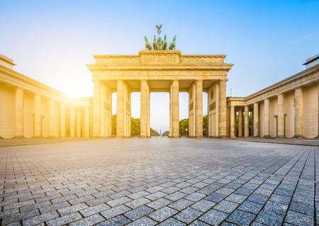 verjas: Famosa Puerta de Brandeburgo Puerta de Brandeburgo, uno de los más conocidos monumentos y símbolos nacionales de Alemania, en la hermosa luz dorada de la mañana al amanecer con destello de lente efecto, Berlín, Alemania