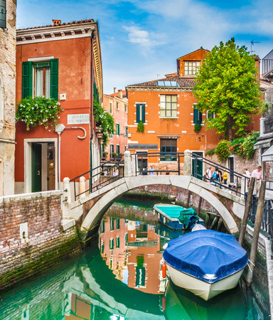 Beautiful scene with colorful houses and boats on a small channel in Venice, Italy