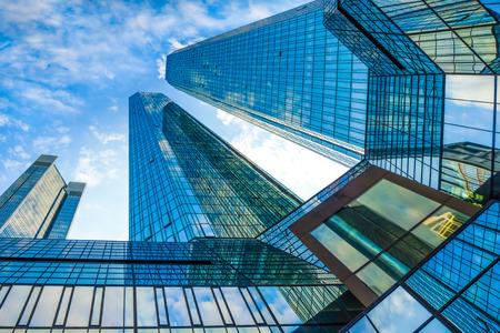 Vista inferior de modernos rascacielos en el distrito financiero contra el cielo azul