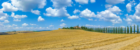 val d'orcia: Beautiful Tuscany landscape with traditional farm house and dramatic clouds on a sunny day in Val dOrcia, Italy Stock Photo
