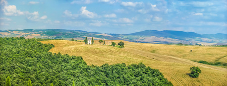 cappella: Panoramic view of beautiful Tuscany landscape with rolling hills and golden harvest fields and famous Cappella della Madonna di Vitaleta in Val dOrcia, province of Siena, Italy Stock Photo