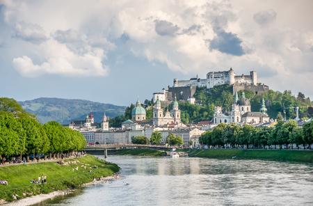 salzach: Beautiful view of Salzburg skyline with Festung Hohensalzburg and Salzach river in summer with dramatic cloudscape, Salzburg, Salzburger Land, Austria Stock Photo