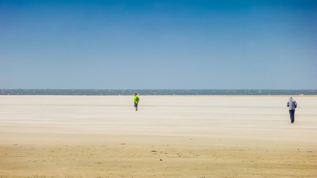 north holland: Two people on the way to the sea at a wide and sandy european north sea beach on a sunny day