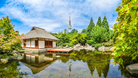 japan sky: Beautiful view of Japanese Garden in Planten um Blomen park with famous Heinrich-Hertz-Turm radio telecommunication tower in the background, Hamburg, Germany
