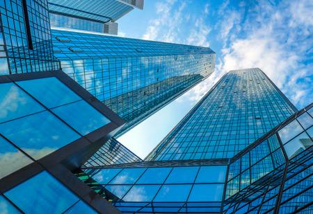 Vista dal basso di moderni grattacieli nel quartiere degli affari contro il cielo blu Archivio Fotografico