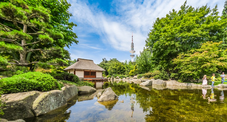 teahouse: Beautiful view of Japanese Garden in Planten un Blomen park with famous Heinrich-Hertz-Turm radio telecommunication tower in the background, Hamburg, Germany