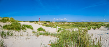 Beautiful dune landscape with traditional lighthouse on the island of Amrum at North Sea, Schleswig-Holstein, Germany