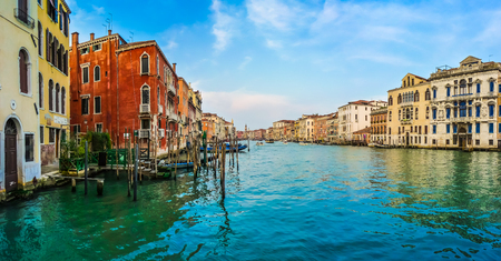 rialto bridge: Panoramic view of Canal Grande with colorful houses and famous Rialto Bridge in the background in Venice, Italy