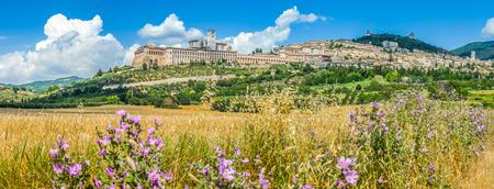 劇的な cloudscape、ゴールデンハー ベスト フィールドおよび野生の花、ウンブリア州、イタリアのアッシジの古代町のパノラマ ビュー
