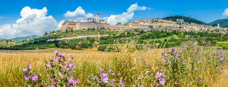 Panoramic view of the ancient town of Assisi with dramatic cloudscape, golden harvest fields and wild flowers, Umbria, Italy