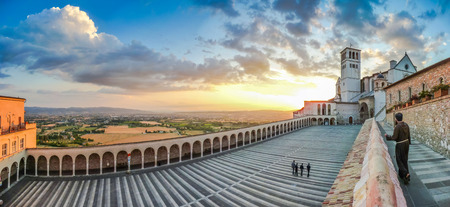 Famous Basilica of St. Francis of Assisi Basilica Papale di San Francesco with monk and Lower Plaza at sunset in Assisi, Umbria, Italy Stock Photo