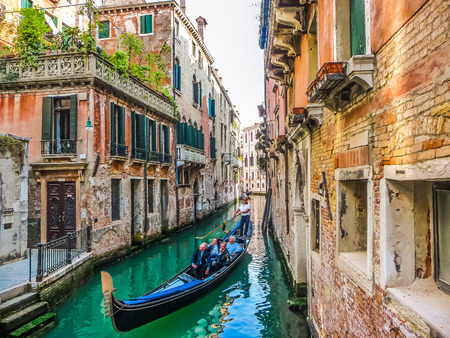 Traditional Gondolas on narrow canal between colorful historic houses in Venice, Italy