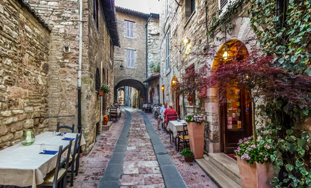 Romantic dinner place in a beautiful alley in the ancient town of Assisi, Umbria, Italy Stockfoto