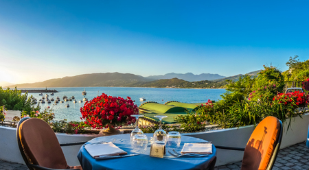 Romantic dinner place with idyllic panoramic view of mediterranean coastal landscape at sunset in golden evening light 版權商用圖片